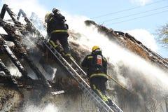 I pompieri affrontano un fuoco del tetto di ricoprire di paglia Fotografie Stock