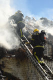 I pompieri affrontano un fuoco su un tetto del cottage Fotografie Stock Libere da Diritti