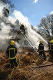 I pompieri affrontano un fuoco in un rurale ricoprono di paglia il cottage del tetto Immagini Stock Libere da Diritti