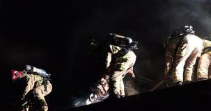 I pompieri che per mezzo dell'ascia ed hanno visto per ventilazione sul tetto implicato archivi video