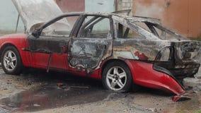 I pompieri con il tubo flessibile versano l'acqua su un'automobile bruciata, veicolo non sono stati assicurati video d archivio