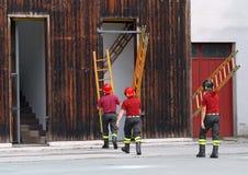 I pompieri durante l'esercitazione antincendio montano una scala Fotografia Stock Libera da Diritti
