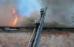 I pompieri estinguono il fuoco da un'alta scala Immagine Stock