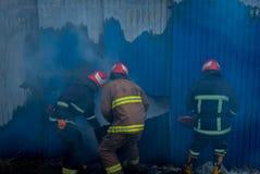 I pompieri lavorano ad un fuoco di costruzione facendo uso di uno strumento di salvataggio della taglierina del metallo durante i Immagine Stock