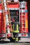 I pompieri nell'azione prendono la scala dall'autopompa antincendio Immagini Stock