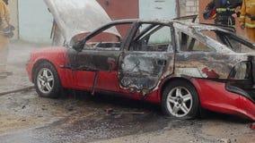 I pompieri o i vigili del fuoco versano l'acqua su un'automobile bruciata stock footage