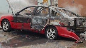 I pompieri o i vigili del fuoco versano l'acqua su un'automobile bruciata video d archivio