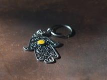 I portachiavi a anello sotto forma di Fatima Hand su un fondo di cuoio marrone Simbolo antico e ricordo turistico moderno tradizi fotografie stock libere da diritti