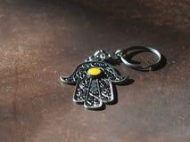 I portachiavi a anello sotto forma di Fatima Hand su un fondo di cuoio marrone Simbolo antico e ricordo turistico moderno tradizi fotografia stock