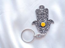 I portachiavi a anello sotto forma di Fatima Hand su un fondo di seta bianco Simbolo antico e ricordo turistico moderno tradizion immagini stock libere da diritti