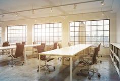 I posti di lavoro in un tramonto luminoso mandano in aria l'ufficio dello spazio aperto Immagine Stock