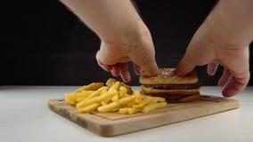 I posti maschii si scolano un hamburger poco appetitoso alto in colesterolo e grassi saturi stock footage