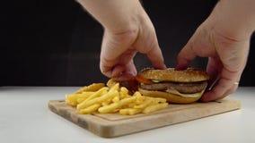I posti maschii si scolano un hamburger poco appetitoso alto in colesterolo e grassi saturi video d archivio