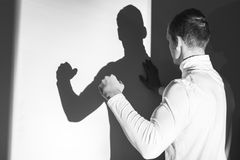 I am so powerful!. Young man demonstrating his muscles to his shadow on the wall Stock Photos
