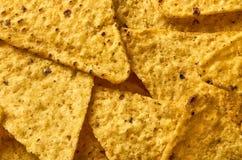 I precedenti del primo piano triangolare giallo dei nacho del cereale fotografia stock