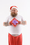 I prepared this present for you. Merry Christmas. Happy fat Santa Claus is holding gift box. He is standing and smiling. Isolated Royalty Free Stock Photography