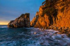 I primi raggi di sole del giorno nel ` Aguia di Cala s su Costa Brava sono Immagini Stock