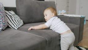 I primi successi di un piccolo 10 mesi del ragazzo Impara stare sui vostri piedi e scendere lo strato archivi video