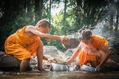 I principianti buddisti stanno pulendo le ciotole e stanno spruzzando l'acqua nella s Fotografie Stock Libere da Diritti