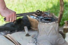 I prodotti metallici sono heated sui carboni nella fornace della forgia Immagine Stock