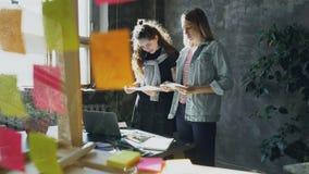 I progettisti allegri sono tavola vicina diritta e foto di scelta per il progetto Le giovani donne stanno avendo relazioni amiche video d archivio