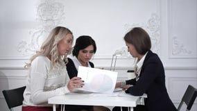 I progettisti femminili che lavorano ad un documento e poi imbrogliano intorno nell'ufficio Timelaps Immagini Stock