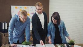 I project manager hanno riunione, analizzano i piani, esaminanti le carte video d archivio
