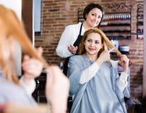 I punti della donna al padrone nel salone dei hairdress radrizzano la lunghezza dei capelli per Fotografia Stock Libera da Diritti
