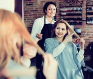 I punti della donna al padrone nel salone dei hairdress radrizzano la lunghezza dei capelli per Immagine Stock Libera da Diritti