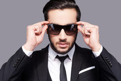 I put the man in manly. Portrait of handsome young man in formalwear adjusting his sunglasses while standing against grey background Stock Photos