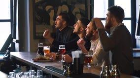 I quattro amici stanno incoraggiando per la loro squadra di football americano favorita che si siede alla tavola della barra con  stock footage