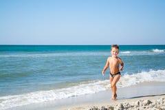 I quattro anni svegli di ragazzo sta correndo nel mare Fotografia Stock