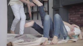 I quattro fratelli e la madre imbrogliano intorno la menzogne sul pavimento nel salone a casa fratellanza Relazione di famiglia video d archivio