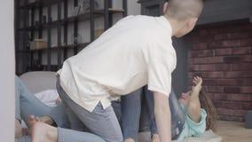 I quattro fratelli e madri allegri imbrogliano intorno la menzogne sul pavimento nel salone a casa fratellanza famiglia video d archivio