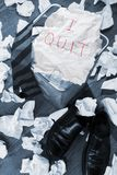 I Quit. Failure concept in blue tone trash can overflowing with paper holding Quit sign with neck tie and shoes Royalty Free Stock Photos