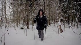 I rörelsemannen som fotvandrar till och med den snöig Forest With Trekking Poles In vintern arkivfilmer