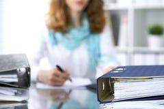 I raccoglitori con le carte stanno aspettando per essere elaborati con la donna di affari o la parte posteriore di segretario nel Fotografie Stock