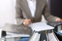 I raccoglitori con le carte stanno aspettando per essere elaborati con la donna di affari o la parte posteriore di segretario nel Fotografia Stock