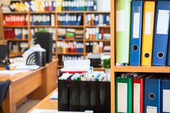 I raccoglitori variopinti dell'archivio sono sugli scaffali della stanza dell'ufficio, copiano lo spazio con fondo vago Fotografie Stock