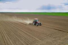 I raccolti della semina dell'agricoltore al campo con il trattore Fotografia Stock Libera da Diritti