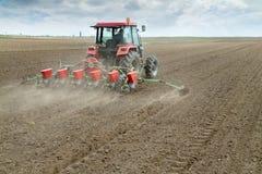 I raccolti della semina dell'agricoltore con la macchina di semina pneumatica Immagine Stock