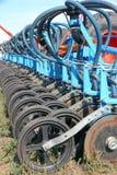 I raccolti di piantatura della seminatrice e del trattore su un campo Fotografia Stock