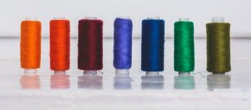 I rad finns det mång--färgade trådspolar som planläggs för needl Arkivbild