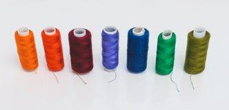I rad finns det mång--färgade trådspolar som planläggs för needl Royaltyfria Bilder