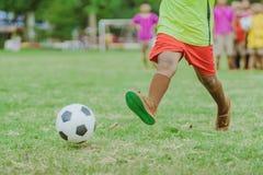 I ragazzi asiatici praticano dare dei calci alla palla per segnare gli scopi immagine stock