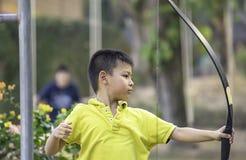 I ragazzi asiatici sono tiro con l'arco nell'avventura del campo fotografia stock