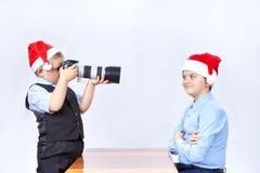 I ragazzi in cappucci di Santa Claus stanno fotografando sulla macchina fotografica Fotografia Stock