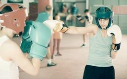 I ragazzi in caschi ed in guanti tengono il pugilato d'allenamento di pugilato Immagini Stock Libere da Diritti