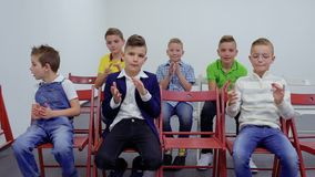 I ragazzi caucasici svegli si siede alle sedie ed all'applauso stock footage