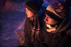 I ragazzi degli adolescenti del bambino di strada ottengono caldi a fuoco nella campagna nevosa di notte dell'inverno fotografia stock libera da diritti